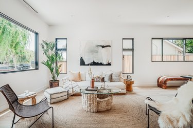 Living room with a round fiber rug, glass and stone coffee table, white sofa with multi-colored pillows, windows of varied sizes, and a palm