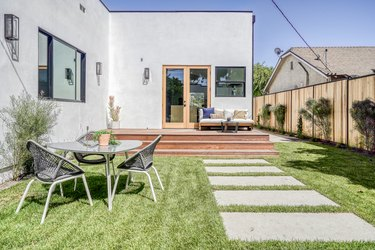 Modern gray house with varying window sizes and casement door. A wood deck with seating. Patio furniture beside a square concrete path.