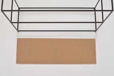 Carboard panel laying next to black metal shelving frame against a white background
