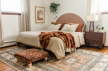 Vintage rug ottoman in a bedroom with neutral, beige, and brown accents