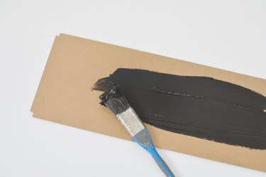 Blue handled paintbrush applying black paint to a rectangular cardboard panel against a white background