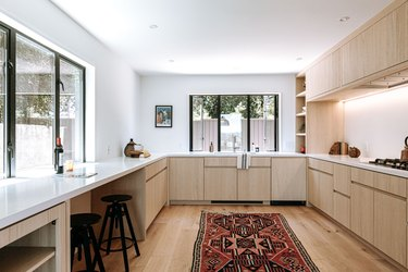 Minimalist kitchen with light wood cabinets and flooring with ornate red rug, and black frame windows