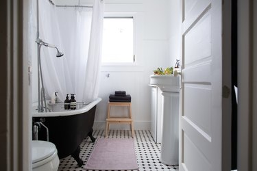 the walls, shower curtain, and most fixtures in this bathroom are white; the floor is black and white tile, and the tub stark black