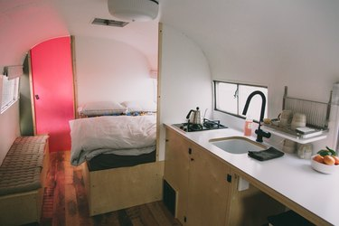 a sink and cooktop are embedded in a long narrow counter; a partition separates the kitchen from the bedroom