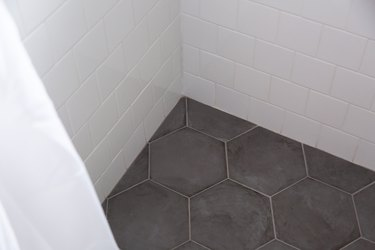 grey hexagonal and white subway tile shower floor and walls