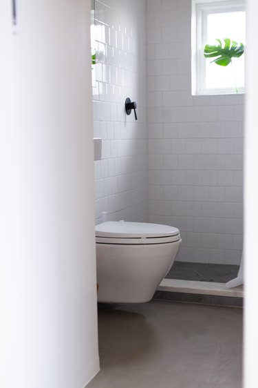 Bathroom with white toilet and white tile and window in shower