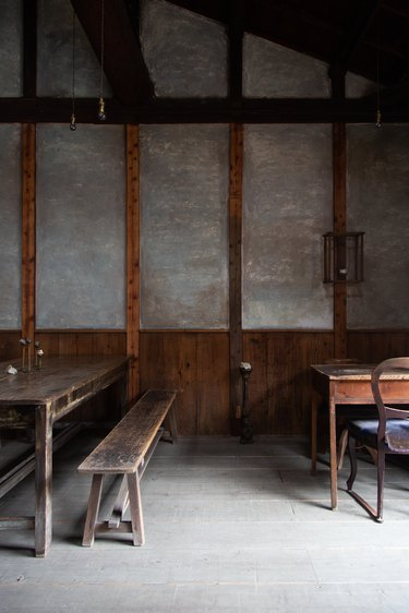 Wooden benches, tables and chairs against concrete walls with wood paneling in low lighting