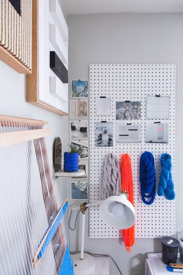 White peg board with materials hung from it, white desk lamp.