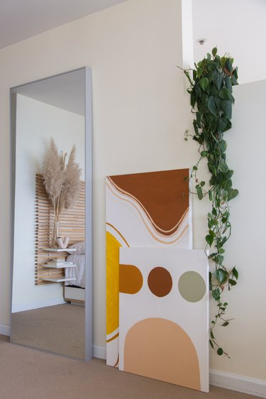 Full-length mirror, next to neutral geometric art, and a Pothos plant on a stepped wall.