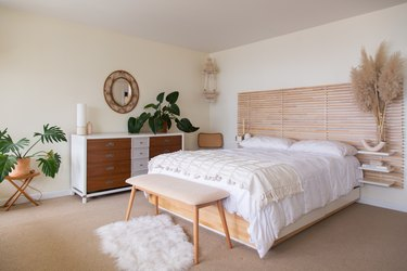 white bedding with throw blanket and wood headboard