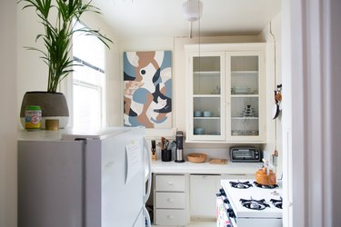 Small white kitchen with windowed cabinets and artwork on wall