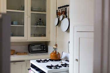 White kitchen with stove and pots and pans hanging on wall with windowed cabinets