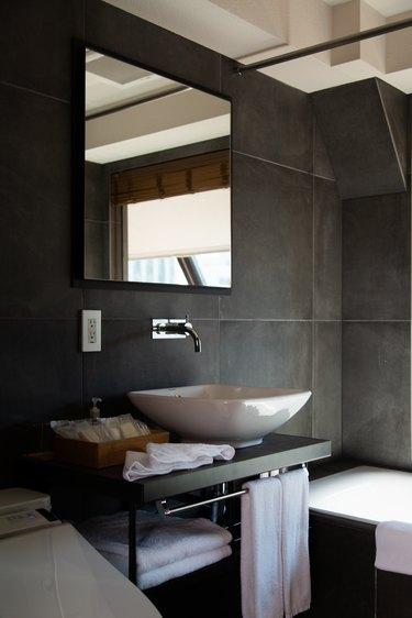 diy bathroom backsplash idea with a white basin sink contrasts with dramatic dark gray walls in the bathroom