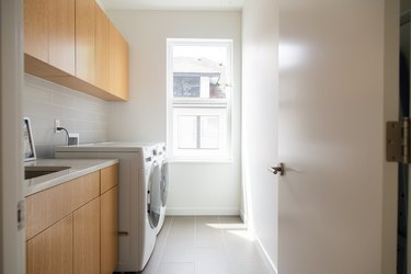 Minimalist laundry room with wood cabinets and white walls