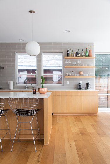 Kitchen with wood cabinets, gray wall tiles, round white pendant light, wall shelves, and Modernist metal wire stools.