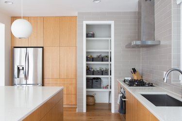 Kitchen with wood cabinets, round white pendant light, white counters, gray tiles, wood floors. A pantry with gray baskets.