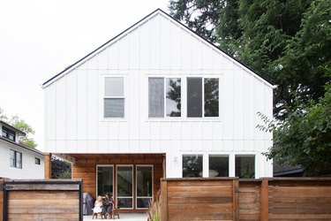 A Contemporary white house, with tall windows, and a horizontal wood fence.
