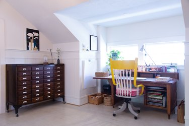 Vintage desk chair, desk and file cabinet in attic home office space.