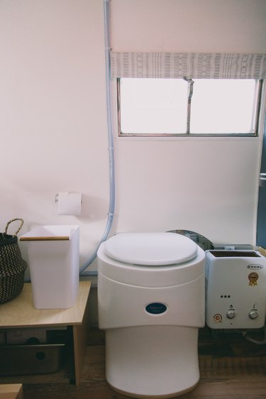 a composting toilet next to the water heater