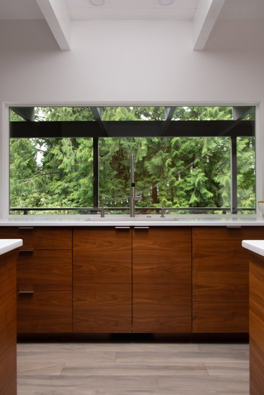 A minimalist contemporary kitchen with wood cabinets and picture windows.