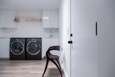 Minimalist laundry room with modern chair and black washer and dryer