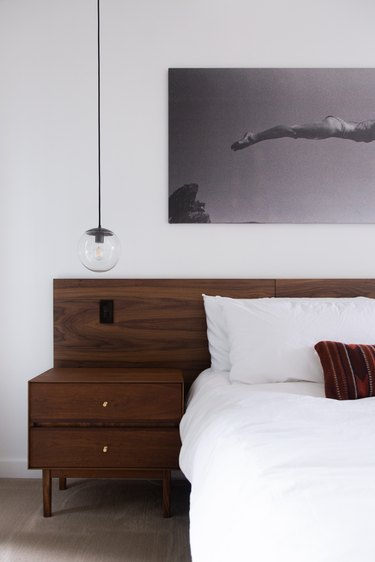 Globe pendant light over a wood nightstand, next to a bed white bedding and a wood headboard.