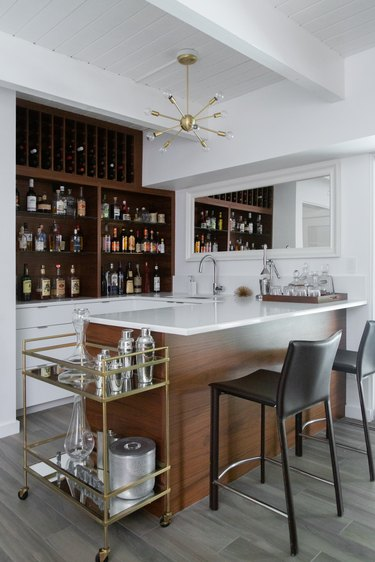 Contemporary Bar with wood, built in wood shelves, modern chandelier, bar cart, black leather bar stools.