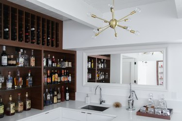 Built-in wood cabinets with bottles of wine and liquor, and a gold modernist bulb chandelier, over a sink.