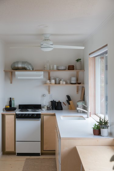 Kitchen corner with stove and open shelving above with dishes and glassware knife, cutting board and coffee pot below kitchen sink under window