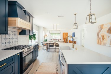 Dark blue kitchen cabinets with gold handles and white countertops. Ornate backsplash by stovetop. Gold lantern pendant lights.
