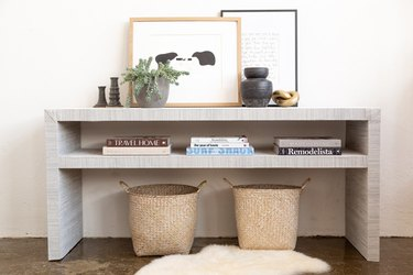 Ikea 'Lack' console table covered with grasscloth pattern wallpaper, decorated with a basket, books, and a plant
