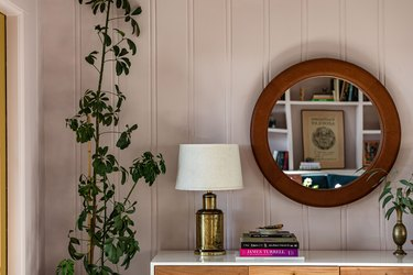 lampshade on brass lamp on credenza next to mirror