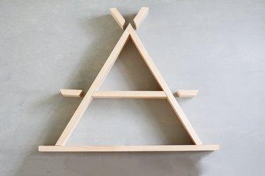 Unconstructed arranged a-frame shelf against grey background