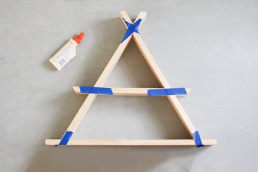 Wooden a-frame shelf taped together along edges with blue painters tape next to glue bottle against grey background