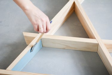 Hand painting inner walls of wooden a-frame shelf against grey background