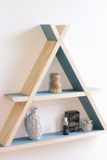 Wooden a-frame shelf with blue inner walls holding small containers on white wall