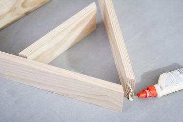 Glue bottle gluing together upper arch of wooden a-frame shelf against grey background