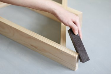 Hand using sanding block to sand edge of wooden a-frame shelf against grey background