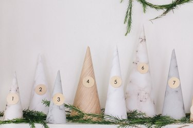 White, gray, beige paper cones with numbers on mantel with pine