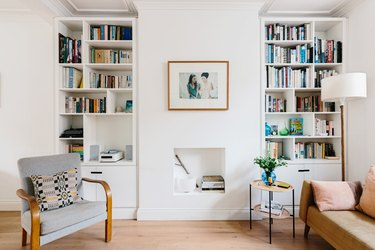Modern living room with bookshelves, leather couch, chair, small side table, and small white fireplace underneath hung framed picture