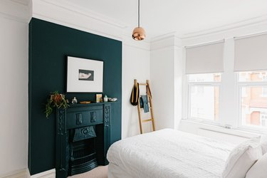 Dark turquoise mantle against white wall in small bedroom with windows and ladder propped against wall