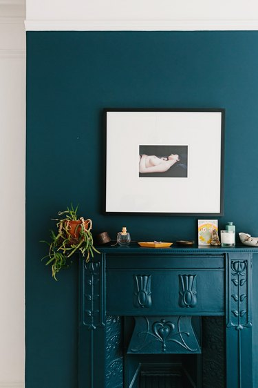 Royal blue mantle and wall against white archway with framed picture and plants