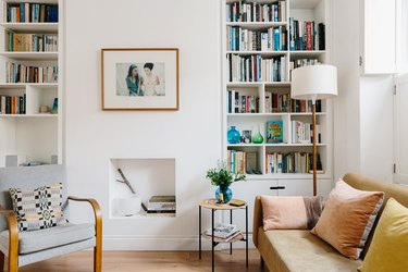 Modern living room with bookshelves, leather couch, chair, and small white fireplace underneath hung framed picture