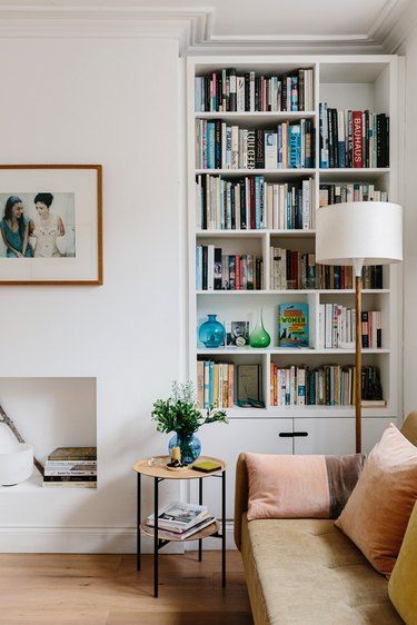 Modern living room with bookshelves, leather couch, lamp, small side table, and small white fireplace underneath hung framed picture