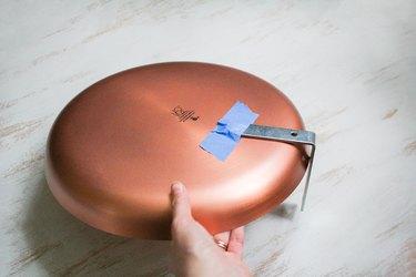 Round dish plate with blue painter's tape holding flat corner brace
