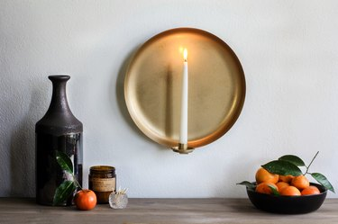 Wall sconce with candle with bowl of tangerines and brown vase