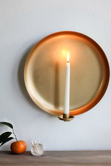 Round wall sconce with tangerine and container of matches
