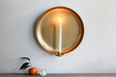Wall sconce with candle with tangerine and container of matches