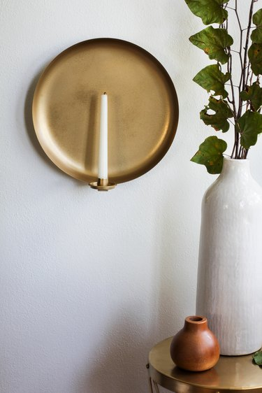 Round wall sconce with candle next to vases