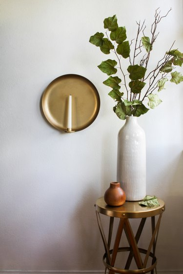 Wall sconce with candle next to small table with vase with plant